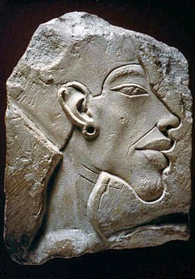 Relief of King Akhenaton. 1340 BCE. Amarna Period. The so-called 'excessive' style at the beginning of the Amarna period is especially obvious with this small relief study. The thin face, heavy eyelids over narrow, slightly slanting eyes, long, hanging chin, long nose, emphasised nasolabial folds, full lips as well as the forward curve of the neck all characterize the early representations of king Akhenaton. The contrast between soft and sharp forms, have been excellently captured