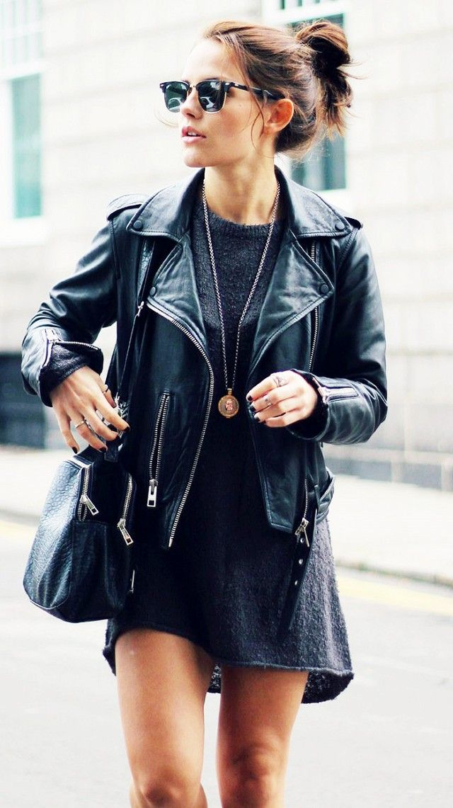 A black dress is worn with a motorcycle jacket, black bag, a pendant necklace, and clubmaster sunglasses