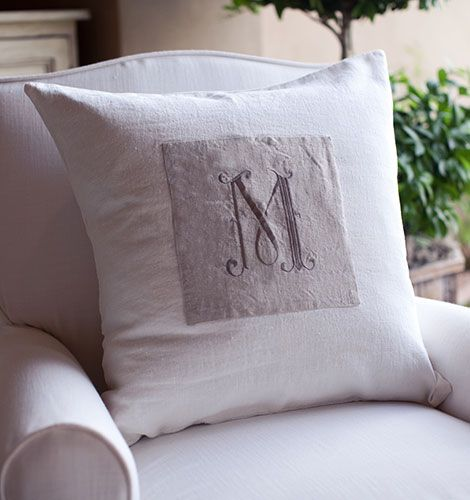 A customized white linen pillow with an all feather and down insert. A vintage, French script monogram is on the front.