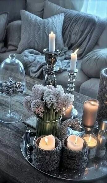 Metal tray holding candles on wooden table top.