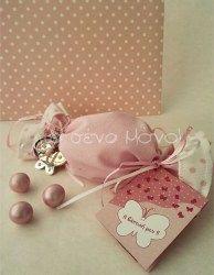 Μπομπονιέρα βάπτισης καραμέλα με κρεμαστή μεταλλική πεταλούδα μπρελόκ από ροζ ύφασμα με πουά λεπτομέρειες, στολισμένη με κορδελάκια λευκά & ροζ απ' όπου κρέμεται το προσκλητήριο.<br> <br> Στην περίπτωση που διαλέξετε την συσκευασία ολοκληρωμένη μπομπονιέρα, η τιμή συμπεριλαμβάνει 5 κουφέτα αμυγδάλου Α΄ποιότητας Χατζηγιαννάκη Super No 2. Αν επιθυμείτε άλλη ποιότητα κουφέτων, παρακαλούμε επιλέξτε όπως θα δείτε παρακάτω.<br> Εάν επιλέξετε άδετη μπομπονιέρα, τα υλικά έ...