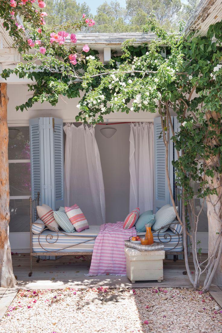 Porche de buganvilla y debajo, una cama de hierro con colchoneta y cojines en rosa y azul 00386391 O