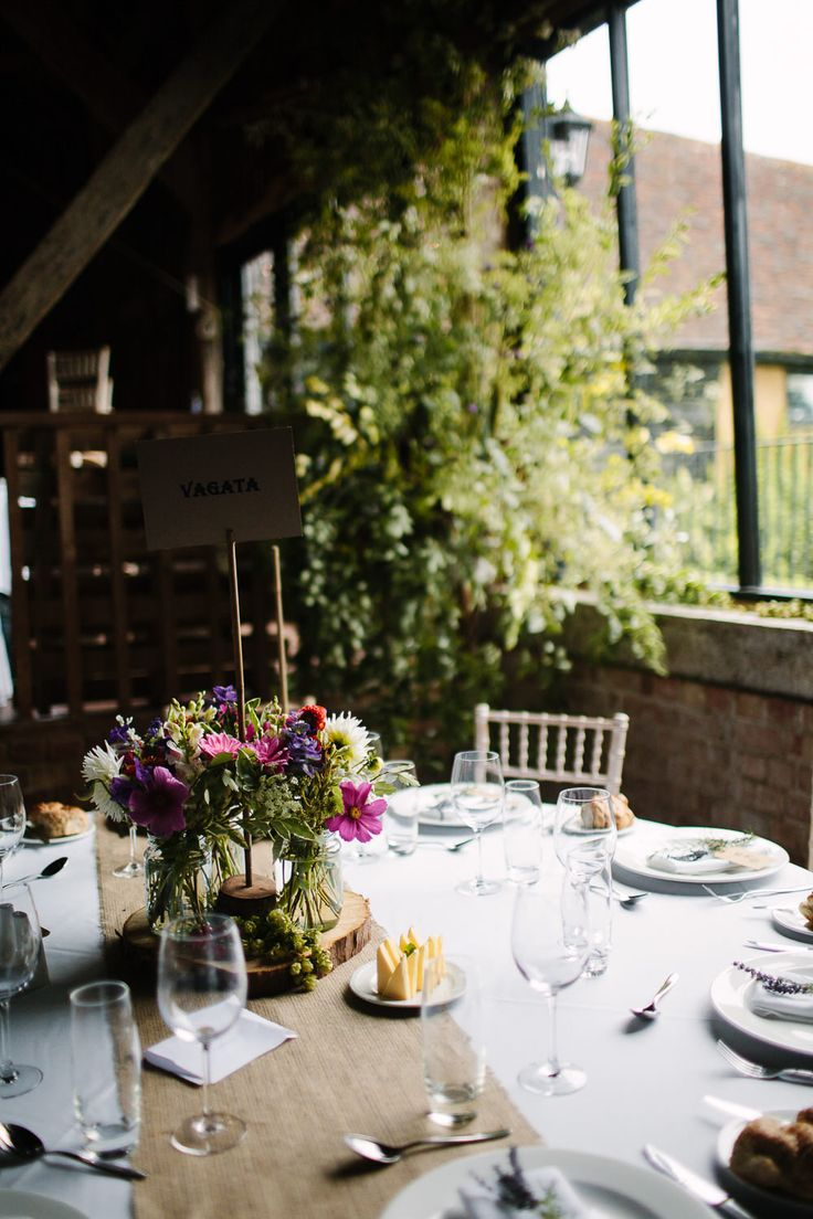 Rustic Tree Slab & Flowers in Jars Table Centrepieces - Joanna Brown Photography | Rustic Wedding at The Great Barn Rolvenden in Kent | Bespoke Bridal Separates | Mis-Match Bridesmaid Gowns | Teal Paul Smith Suit
