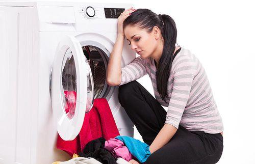 Frau wäscht Wäsche in der Waschmaschine