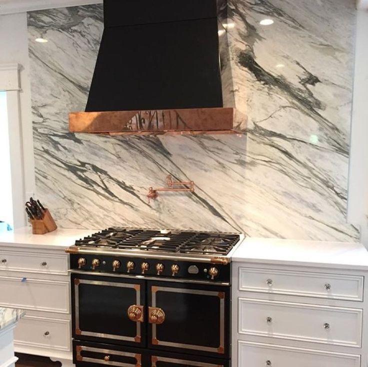stunning kitchen with black range, hood and Calcutta marble slab backsplash