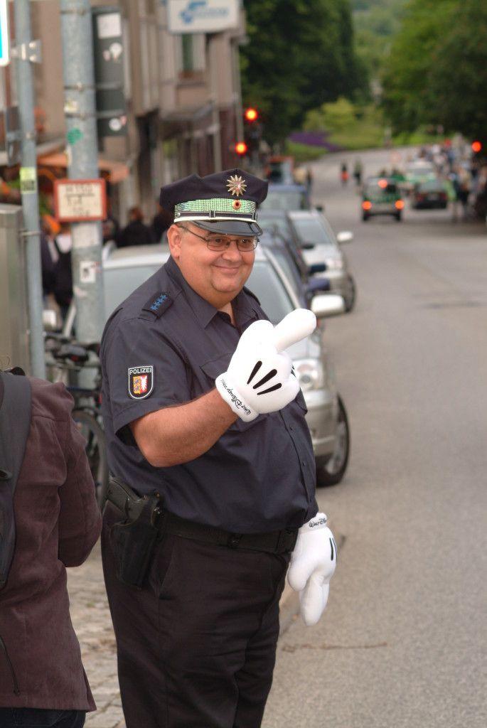 """Hier kommen wir in einen absoluten Grenzbereich. Dieser Polizist hat den Verkehr geregelt anlässlich des Besuchs hochrangiger Politiker auf der Kieler Woche.Eigentlich darffst Du das Foto ohne seine Genehmigung nicht veröffentlichen. Nun spielen hier besondere Aspekte eine Rolle. Der Polizist hat sich mit den Handschuhen """"verkleidet"""", durch die Uniform erweckt er in Kombination mit den Handschuhen Aufmerksamkeit. Es gibt neben diesem Foto weitere Aufnahmen, wo er sichtbar mit anderen…"""