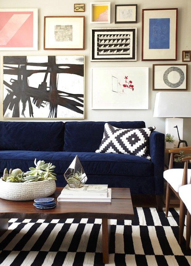 Dark blue couch with brown coffee table  Gallery wall over a navy sofa, designed by Orlando Soria, via @sarahsarna.