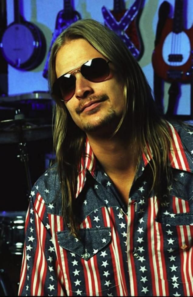 Kid Rock pictured in a Confederate-themed shirt. A Confederate flag painted on one of his guitars can be spotted behind him.