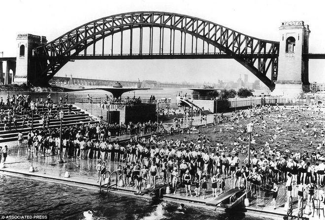 1940: New Yorkers swim in the Astoria public pool with the Hell Gate railroad bridge in the back.