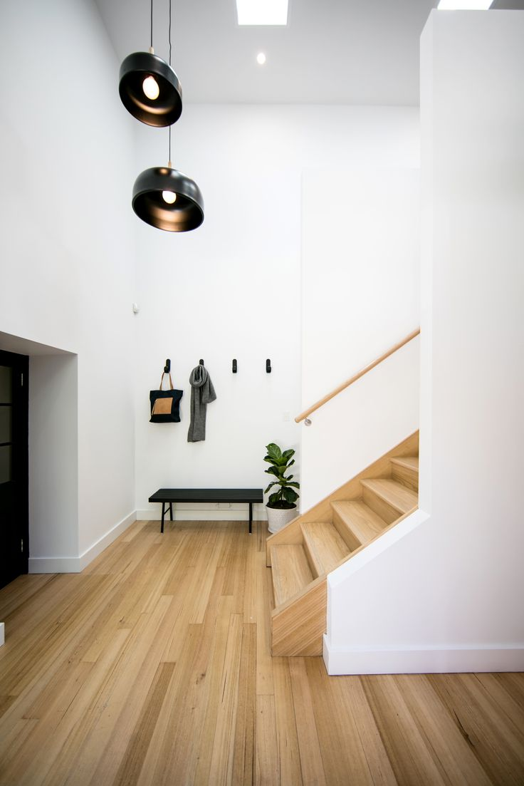 The entry hall - linking old and new - includes oak timber flooring, bold coat hooks by Hay and striking drop pendants.