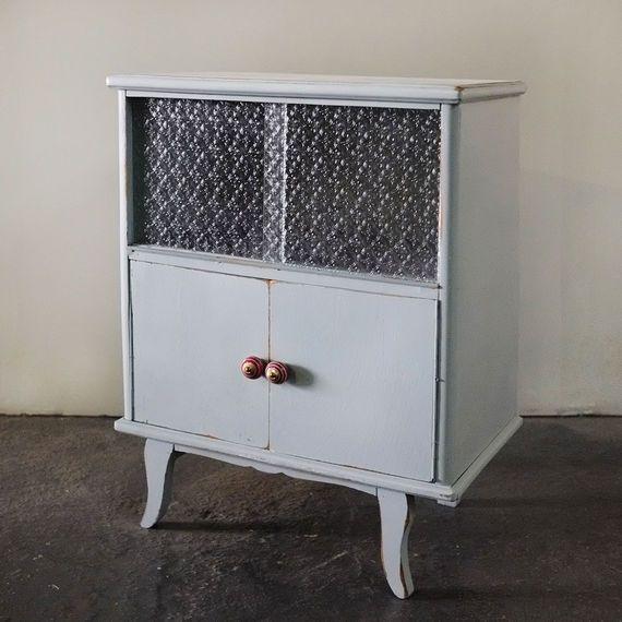 שידה מקסימה, חודשה ונצבעה בגוון תכלת אפרפר נוספו דלתות שעשויות מזכוכית סבתא. בתחתית המדף הודבק טפט רהיטים