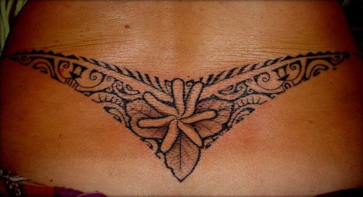 "on Lower Back of Maori Polynesian style for Women representing a ""v"" or boomerang with a flower and leaves in the center and the wings fullfilled with multiple ancient symbols from the Traditional Marquesas's Ancient TATAU. Designed & Tattooed by Manao Tiki Tattoo Toulon"