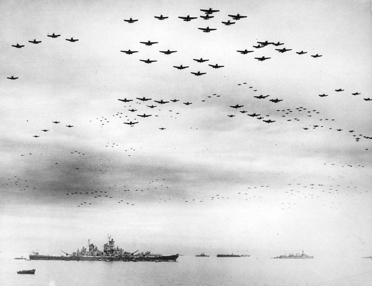 Dozens of F4U Corsair and F6F Hellcat fighter planes fly in formation over the USS Missouri, while the surrender ceremonies to end World War II take place aboard the U.S. Navy battleship, on September 2, 1945.