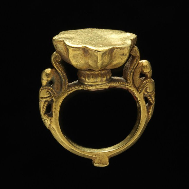 Gold ring, 17th century, India, Deccan, Max. Diam.: 1 1/8 in. (2.9 cm) Diam. of bezeL. 3/4 in. (1.9 cm). The flower-shaped bezel of this ring is flanked by two birds resting on scroll brackets. Birds of this form are popular motifs found on South Indian jewelry, often seen in symmetrical decoration similar to this example, but also appear as engraved precious stones. The physiology of these birds suggests that they are most likely parrots which are prevalent in Deccani painting.