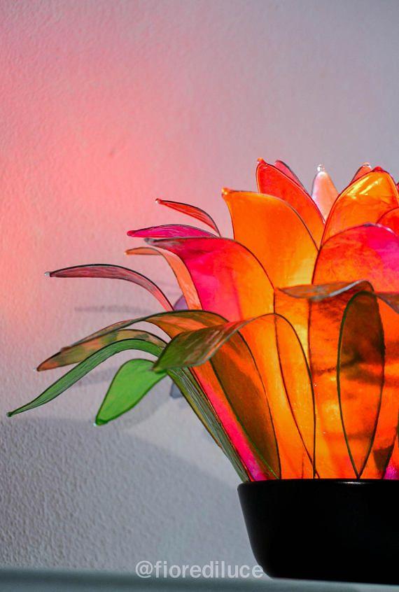 Anemone rosso ciliegia, una affascinante lampada rossa, dal profumo di estate, di luce e colori forti; con i suoi toni caldi accompagnerá lambiente anche di giorno, come un bellissimo oggetto decorativo, e nelle grige giornate invernali risplenderá come un piccolo sole.  Ispirata al fiore di anemone e al colore rosso ciliegia, con i suoi petali rossi, arancio, fuxia e giallo crea sorprendenti sfumature in differenti angolazioni e riflette un dolce alone color ciliegia.  La lampada é creata…