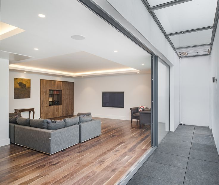 With a full width lightwell constructed with a walkable glass and grille cover - maximum light and no garden lost.  Another basement construction by London Basement