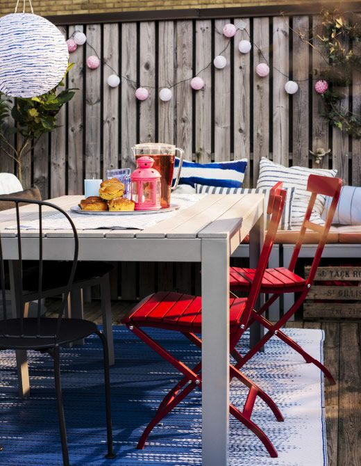 An outdoor dining table with a lantern, a plate of pastries, and juice.