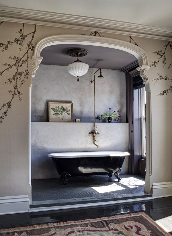 A black tub with brass fixtures is set in a nook | archdigest.com