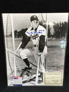 LARGE BLACK AND WHITE VINTAGE PHOTO OF DUKE SNIDER AS A BROOKLYN DODGER, STANDING NEXT TO A BATTING CAGE AT VERO BEACH SPRING TRAINING FACILITY. THE PHOTO HAS BEEN HAND SIGNED IN BLUE SHARPIE INK AND IS INSCRIBED HOF 80. IT COMES WITH TWO COAS INCLUDING ONE FROM SNIDER PASSED AWAY IN 2011 WHILE LIVING IN FALLBROOK. IN ADDITION TO BEING A MEMBER OF MLB HALL OF FAME, HE WAS ONE OF THE THREE ICONIC NEW YORK CENTER FIELDERS IN THE 1950S, WILLIE, MICKEY AND THE DUKE. MEASURES 20H X 16W