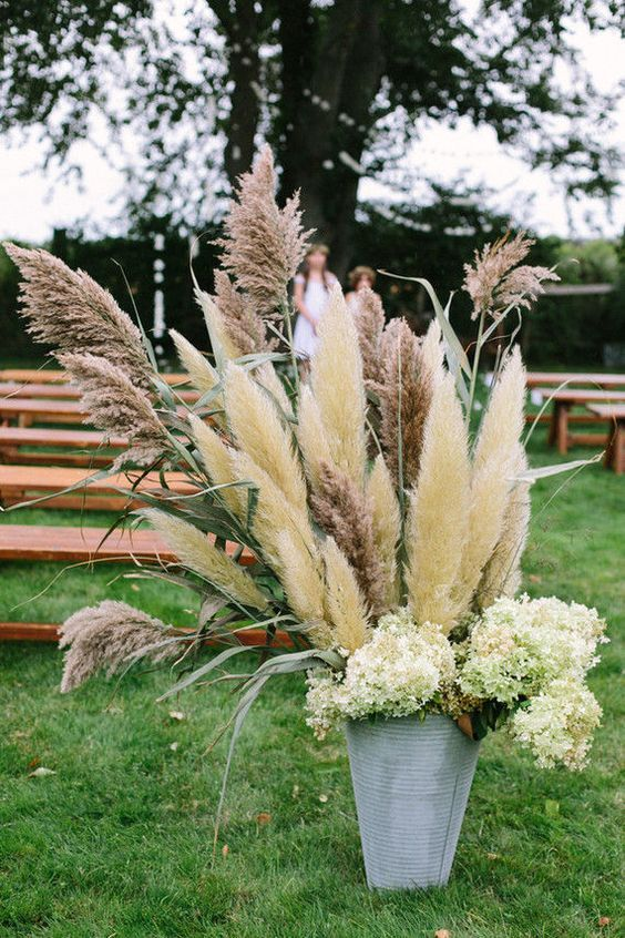 rustic wedding ideas - overflowing bucket filled with an eclectic mix of bucolic greens / http://www.himisspuff.com/pampas-grass-wedding-ideas/5/