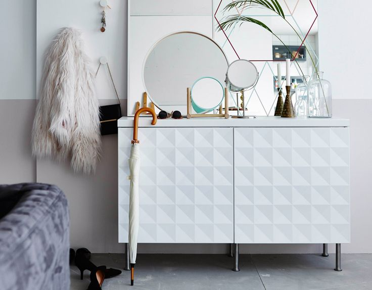 A hallway cabinet made of two white kitchen cabinets with textured doors and stainless steel legs.