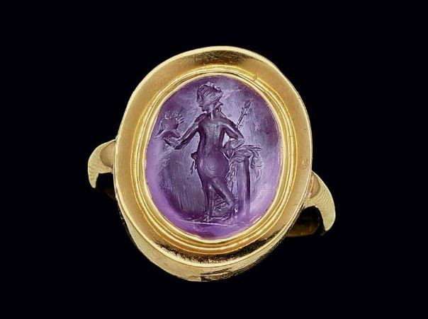 A ROMAN AMETHYST RINGSTONE CIRCA 1ST-2ND CENTURY A.D. The convex oval stone engraved with Venus Victrix, nude but for a mantle draped around her waist, leaning against a column, holding a spear in her left hand and a helmet in her outstretched right; mounted as a ring in a modern gold setting   Christie's