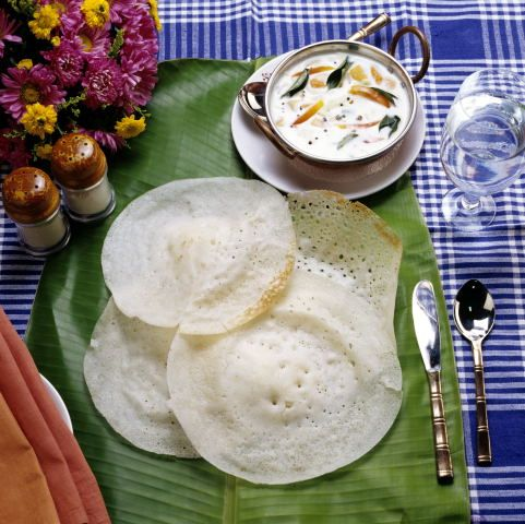 Traditional Kerala breakfast food- appams (rice pancakes) with coconut-based veggie, chicken, beef, or egg curry