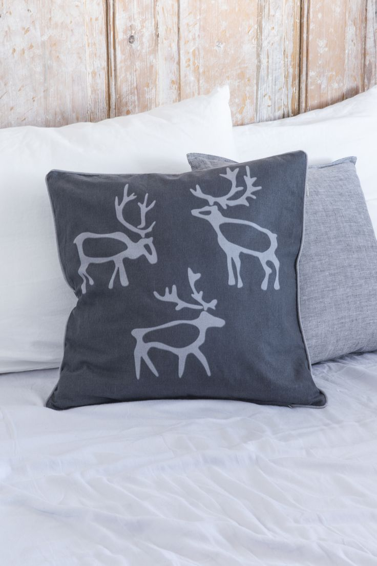 Saaga Cushion Cover | Pentik | The textiles of Saaga series bring a hint of northern touch to your table setting. Designed by Minna Niskakangas, the reindeer pattern of Saaga has been inspired by northern rock paintings and warm gray shades of deadwood.