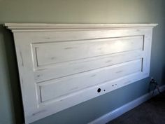King headboard from old door. Annie Sloan pure white chalk paint, then distressed lightly and waxed with clear wax. Attached to wall with French cleat.