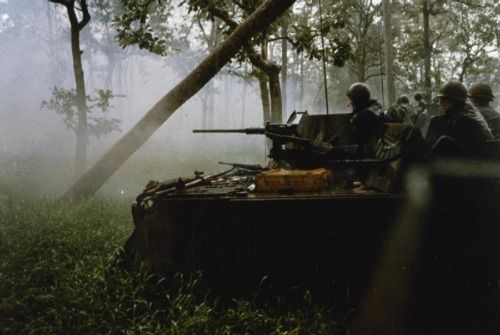 Captain Elbridge G Fish II, Commander of F Troop, 2 Sqdn, 11 Armored Cavalry Regiment (the Blackhorse Regiment), US Army, orders a reconnaissance by fire as the Regiment's M-113 Armored Personnel Carriers advance in line at the base of Hill 95 in the Fish Hook area, 15 June 1970.