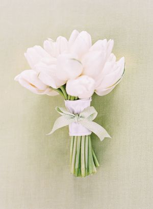 White tulip bouquets for the wedding party. Add in the small touch of a matching ribbon to bind it all together!