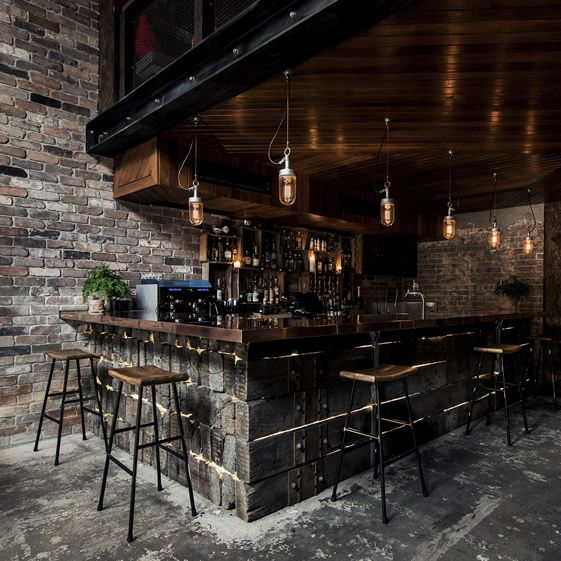 The bar downstairs is made of reclaimed railway sleepers that have been lashed together with ratchet straps, and it's topped with a lovely polished copper top that zings against the weathered wood. A mezzanine level set back from the entrance opens up the space to its full cavernous effect....