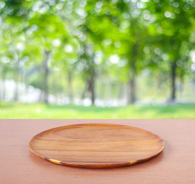 Bandeja de madeira redonda vazia na mesa sobre o fundo da árvore borrada Foto Premium