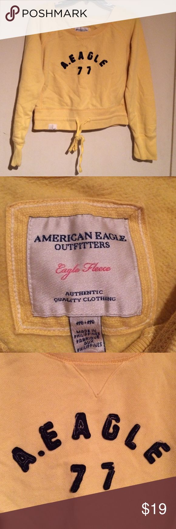 """American Eagle Outfitters yellow sweater This is American Eagle Outfitters yellow sweater that ties in the front for extra support and just looks cute. The front says """"A. Eagle 77"""". Is lightly worn. No noticeable flaws. American Eagle Outfitters Sweaters Crew & Scoop Necks"""