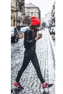 Un total look noir avec des baskets et un bonnet rouges