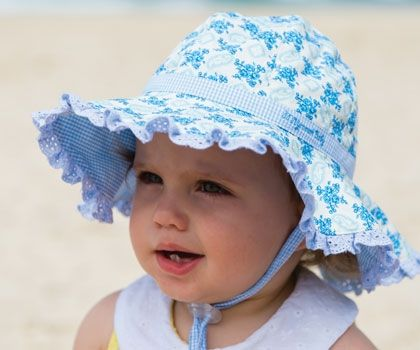 The most gorgeous baby hat you will find. It is fully reversible 100% cotton. One side has a blue floral print with a gingham strip around the crown and a baby blue broderie anglaise frill around the brim. The second side is all blue gingham with the baby blue broderie anglaise frill.