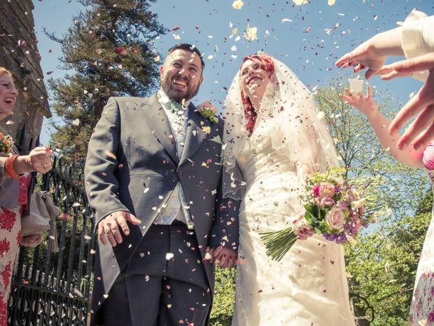Guests shower Jo McCann and Craig Davis with confetti after their ceremony at St Leonards Church in #Upton #Gloucester. Image © A Great Pose. #realweddings
