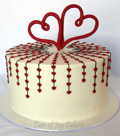 Valentine's Day cake with buttercream hearts and fondant heart topper.