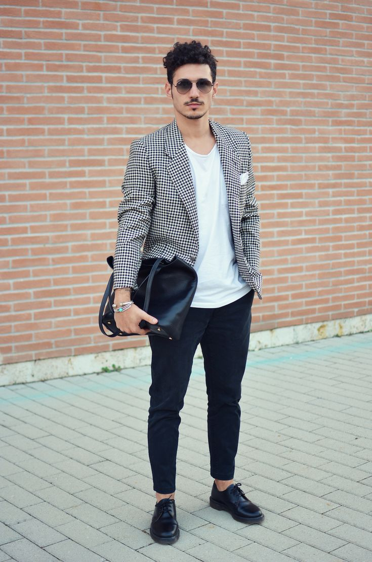 Acheter la tenue sur Lookastic: https://lookastic.fr/mode-homme/tenues/blazer-t-shirt-a-col-rond-pantalon-chino-chaussures-derby-sac-fourre-tout--lunettes-de-soleil/4989 — Chaussures derby en cuir noir — Pantalon chino bleu marine — Sac fourre-tout en cuir noir — T-shirt à col rond blanc — Pochette de costume blanc — Blazer en pied-de-poule noir et blanc — Lunettes de soleil noir