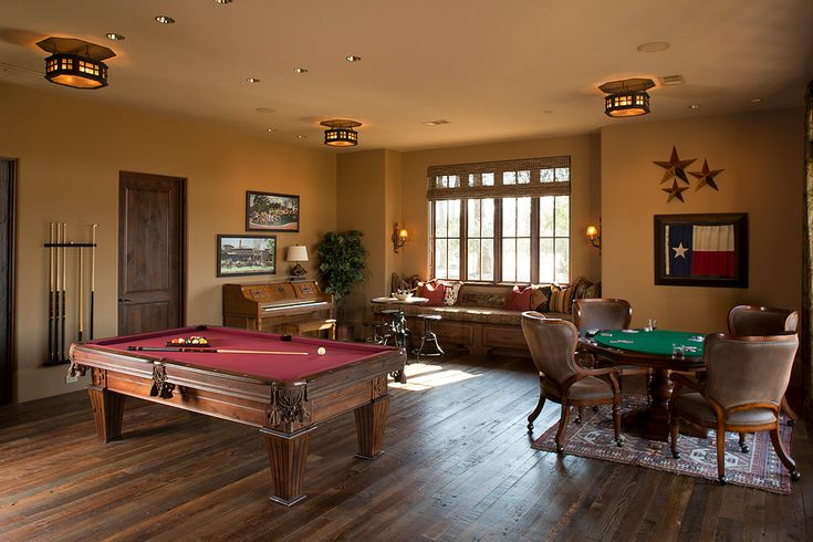 Saloon western southern inspired game room billiards and card table, piano, Texan decor. A warm, inviting, traditional rustic home in Texas. Styled with warm and deep woods, iron accents, rustic tile and wood floors, traditional furniture, and plenty of greenery. #traditionalinteriordesign #rusticinteriordesign #traditional #rustic #interiordesign #architecture For more interior design & architecture click here: https://www.cdgai.com/texas-lodge