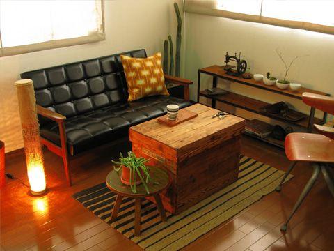 木箱をテーブルに、カリモクの定番ソファに置かれたクッションのテキスタイルのレトロ感が洒落ている。