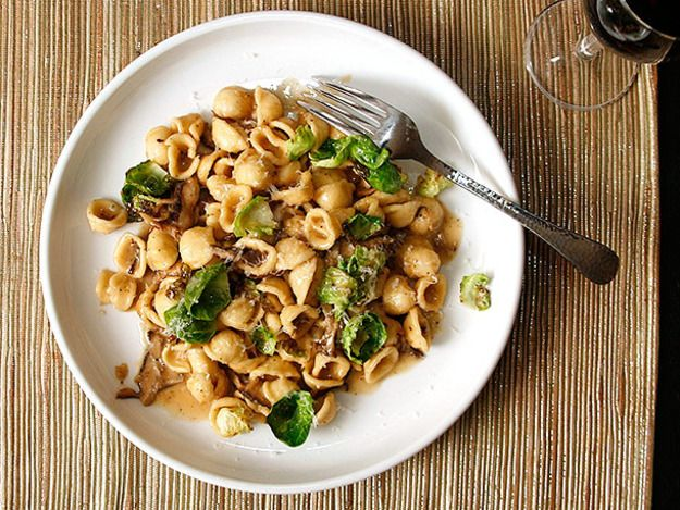 A quick dinner of orecchiette pasta tossed in a clingy sauce made with mushrooms, shallots, thyme, and brussels sprouts leaves.
