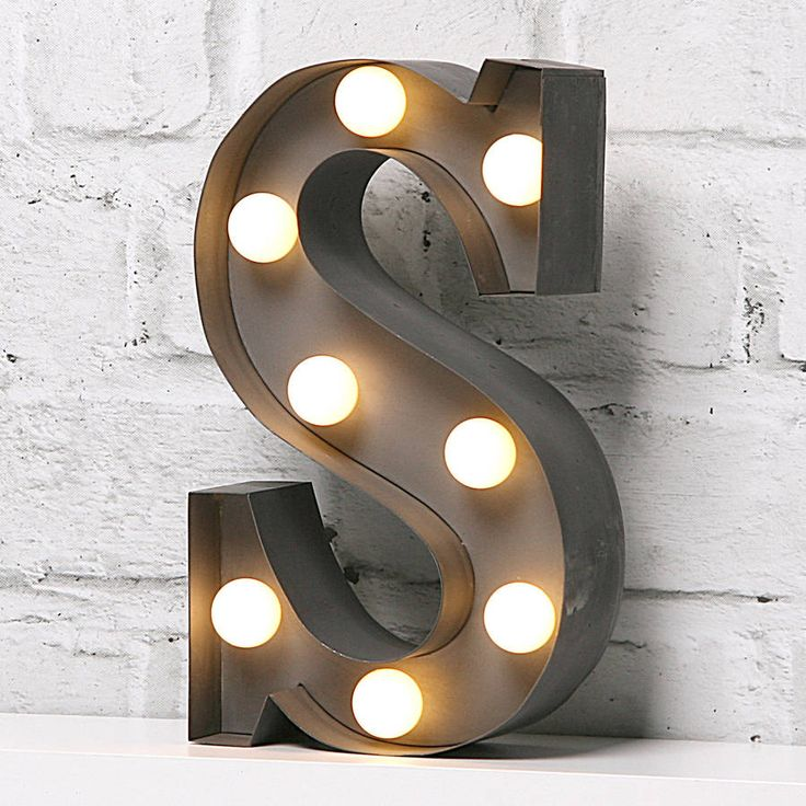 """9"""" carnival light LED battery powered metal letter light.Available in industrial silver finish. Please note each shape is finished by hand and may vary from photo. For indoor use only.Illuminated letters make a great personalised gift. These 9"""" lights are a smaller cute version of our larger lights. Great freestanding on bookcase or shelf with hanger at back of letter for wall mounting. Battery powered LED lights give a soft glow. LED Lights have life-time of up to 30,000 hours. Battery ..."""