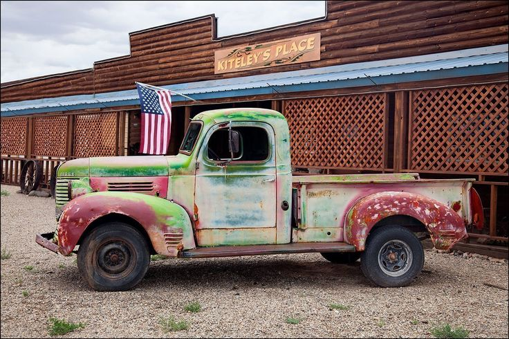 Photograph of old rusty truck and American flag in front of a building off of a country road. Large wall art décor photography for your living room, bedroom, kitchen, dining room, hallway or office. Image title: Patriot Truck This wall art image is of a rusty farm truck This art decor photograph is from my photography series of classic cars and trucks and was photographed off of a country road. All photographs are original and photographed by artist Bob Estrin. Photographs are available in…