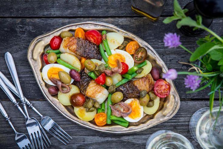 Koka potatisen, äggen och haricots vertsen. Dela torsken i mindre bitar och bryn den i panna med skinnsidan nedåt tills skinnet fått en fin krispig yta. Vänd och stek fisken färdig på svag värme. Dela tomaterna, potatisen, äggen och haricots vertsen.Brynt sardellsmör: Smält smöret och låt det få en gyllene färg. Skär sardellerna i grova bitar och lägg ner i smöret. Låt allt bli varmt.
