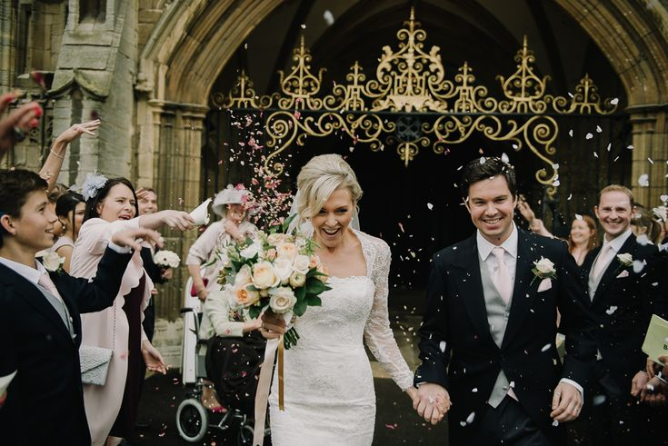 Confetti photography as Bride & Groom exit the wedding ceremony - Image by Modern Vintage Weddings - Suzanne Neville Lace 'Antonia' Wedding Dress and Jenny Packham Bridal Accessories for a traditional wedding ceremony in Peterborough Cathedral and a reception at Stapleford Park. Bridesmaids wear pale pink dresses and Groomsmen in tails.
