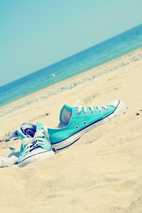 light blue converse on the beach.