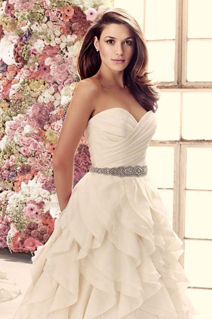 robe de mariée haute couture coupe princesse à volants, avec décolleté croisé et ceinture strass