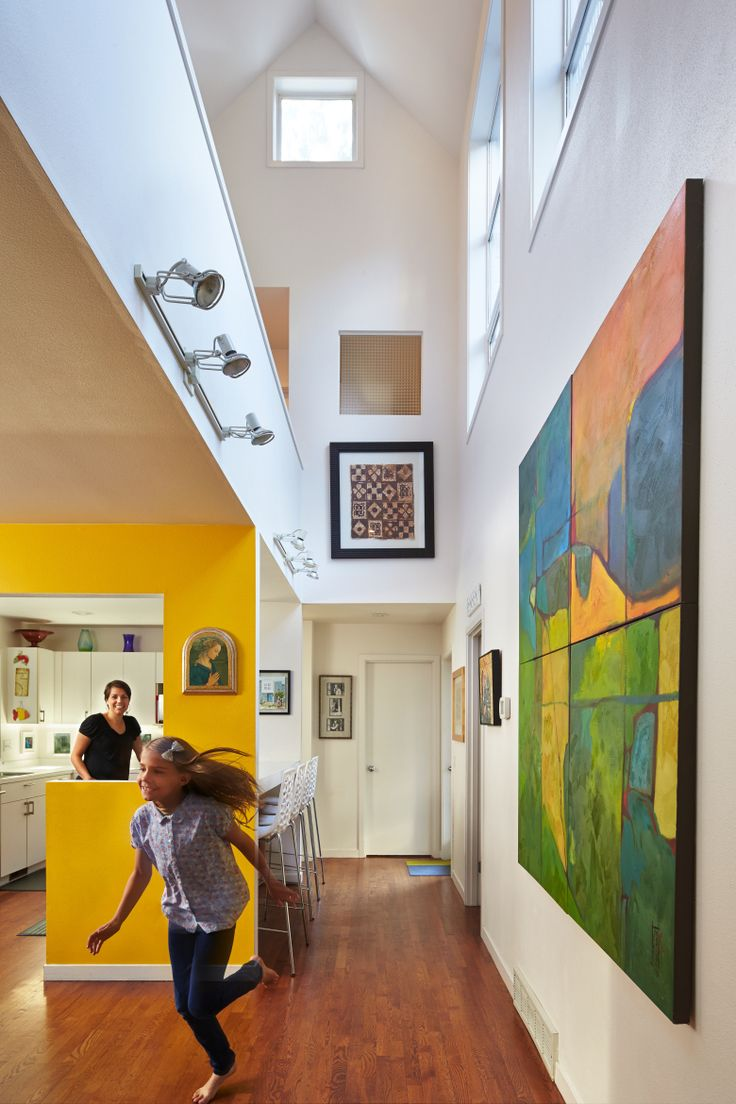 """Carmen appreciates her husband's passion for design. She likes the functionality of modern design. """"It's all about stripping stuff away,"""" she says. The painting is by Jeremy's sister, Jennifer Jensen Mohanty. Behind this wall is a storage room, furnace room and the garage, a buffer between family and freeway. (Benjamin Benschneider)"""