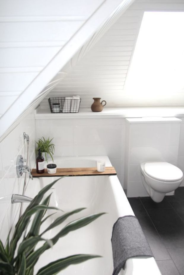 Minimalist bathroom with sloping ceiling and skylight.